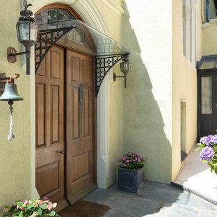 デヴォンの広い両開きドアヴィクトリアン調のおしゃれな玄関ドア (白い壁、濃色木目調のドア) の写真