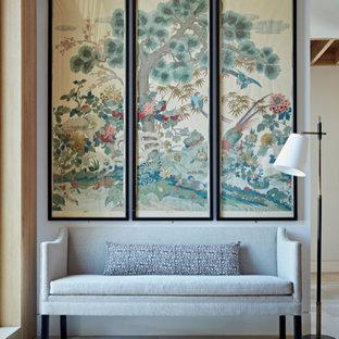 ハンプシャーの巨大な回転式ドアコンテンポラリースタイルのおしゃれな玄関ホール (ライムストーンの床、木目調のドア、ベージュの床、表し梁) の写真