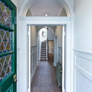Esempio di un corridoio vittoriano con pareti bianche, pavimento in legno massello medio, una porta singola e una porta verde