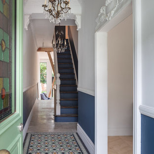 Photo of an eclectic hallway in Manchester with a single front door, a green front door, multi-coloured walls and multi-coloured floors.