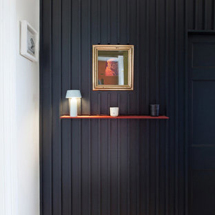 Design ideas for a contemporary entrance in Edinburgh with black walls, light hardwood flooring, a single front door, a yellow front door and beige floors.