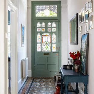Inredning av en klassisk mellanstor ingång och ytterdörr, med vita väggar, klinkergolv i keramik, en enkeldörr, en grön dörr och flerfärgat golv