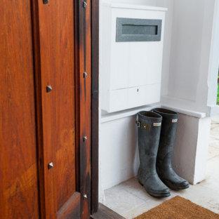 На фото: маленький тамбур в стиле кантри с белыми стенами, полом из известняка, одностворчатой входной дверью, входной дверью из темного дерева и бежевым полом