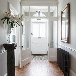サセックスの広い片開きドアトランジショナルスタイルのおしゃれな玄関ロビー (グレーの壁、淡色無垢フローリング、白いドア、茶色い床、格子天井、パネル壁) の写真