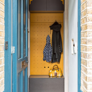 Entryway - small contemporary entryway idea in London with yellow walls and a blue front door