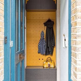 Inredning av ett modernt litet kapprum, med gula väggar, en enkeldörr och en blå dörr