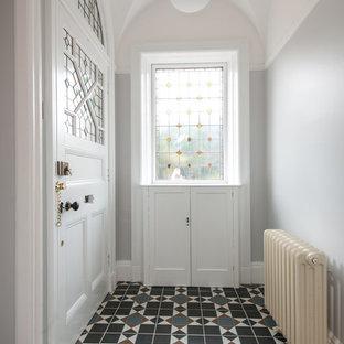 На фото: вестибюли среднего размера в викторианском стиле с серыми стенами, одностворчатой входной дверью, белой входной дверью и полом из керамической плитки