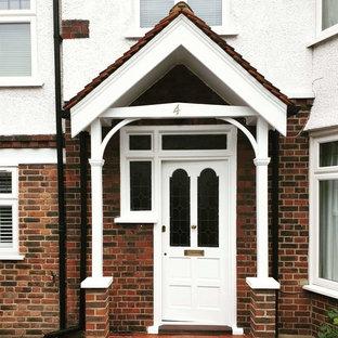 Foto på en mellanstor vintage ingång och ytterdörr, med röda väggar, betonggolv, en enkeldörr, en vit dörr och grått golv