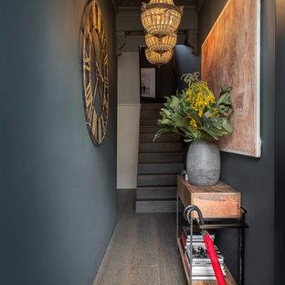 ロンドンの中サイズのエクレクティックスタイルのおしゃれな玄関ホール (無垢フローリング、茶色い床、黒い壁) の写真