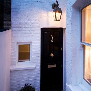Foto di una piccola porta d'ingresso con pareti bianche, pavimento in pietra calcarea, una porta singola e una porta nera