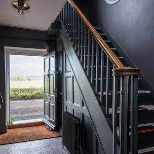 Idee per un corridoio tradizionale di medie dimensioni con pareti nere, una porta singola e una porta nera