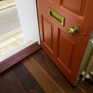 На фото: маленькая входная дверь в классическом стиле с бежевыми стенами, темным паркетным полом, одностворчатой входной дверью и розовым полом с