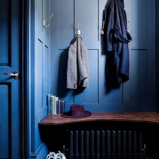 Medium sized victorian boot room in London with blue walls and black floors.