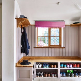 Inspiration for a country wall paneling mudroom remodel in Cheshire with pink walls