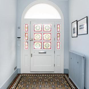 Ejemplo de hall tradicional, grande, con paredes azules, puerta simple, puerta blanca y suelo marrón
