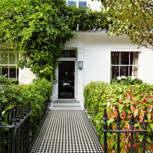 This is an example of a large classic front door in London with a single front door, a black front door, white walls and ceramic flooring.