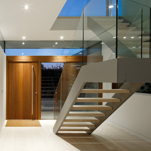 This is an example of a contemporary entrance in Hampshire with white walls, light hardwood flooring, a pivot front door and a medium wood front door.