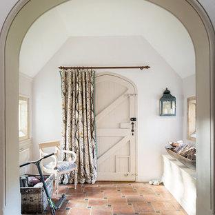Lantlig inredning av en entré, med vita väggar, klinkergolv i terrakotta, en enkeldörr och rött golv