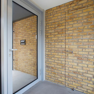 Inspiration for an industrial entryway remodel in London with a glass front door