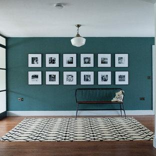 Exempel på en mellanstor modern foajé, med gröna väggar, mörkt trägolv, brunt golv och glasdörr