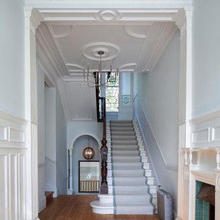Exempel på en klassisk foajé, med vita väggar, mellanmörkt trägolv och brunt golv