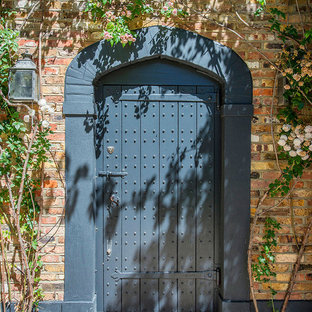 Idee per una porta d'ingresso tradizionale di medie dimensioni con pareti rosse, una porta singola e una porta blu