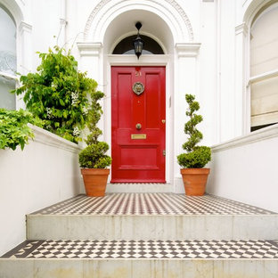 Photo of a classic front door in London with white walls, porcelain flooring, a single front door, a red front door and multi-coloured floors.