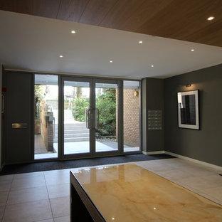 Foto de vestíbulo actual, de tamaño medio, con paredes grises, moqueta, puerta doble, puerta metalizada y suelo multicolor