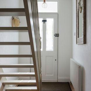 Elegant medium tone wood floor entryway photo in London with white walls and a white front door