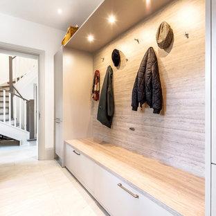 Aménagement d'une entrée classique avec un vestiaire, un mur blanc et un sol blanc.