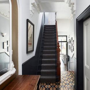 ロンドンの広い片開きドアヴィクトリアン調のおしゃれな玄関ドア (磁器タイルの床、グレーのドア、マルチカラーの床、レンガ壁) の写真