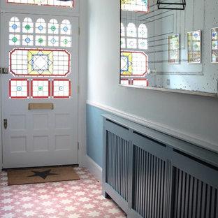 ロンドンの広い片開きドアヴィクトリアン調のおしゃれな玄関ホール (青い壁、セラミックタイルの床、ガラスドア、ピンクの床) の写真