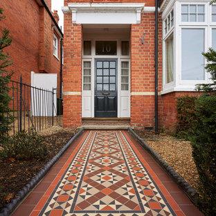 Ispirazione per una porta d'ingresso bohémian con pareti rosse, una porta singola, una porta nera e pavimento rosso