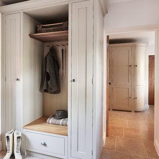 Idéer för att renovera ett litet vintage kapprum, med vita väggar och kalkstensgolv