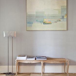 Cette photo montre une grande entrée tendance avec un mur gris et un sol en bois clair.