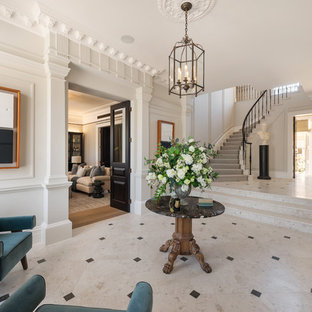 Design ideas for a large traditional foyer in London with white walls, marble flooring and beige floors.