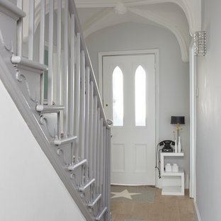 Inspiration for a medium sized contemporary hallway in London with grey walls, light hardwood flooring, a single front door and beige floors.
