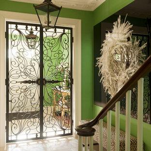 Réalisation d'une entrée bohème de taille moyenne avec un mur vert, un sol en travertin et une porte métallisée.