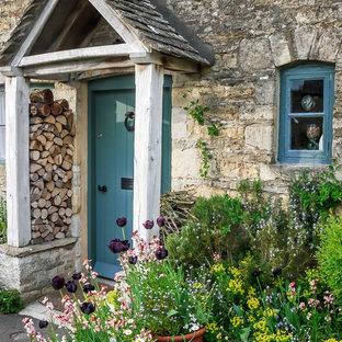 Стильный дизайн: входная дверь в стиле кантри с одностворчатой входной дверью, синей входной дверью и серыми стенами - последний тренд