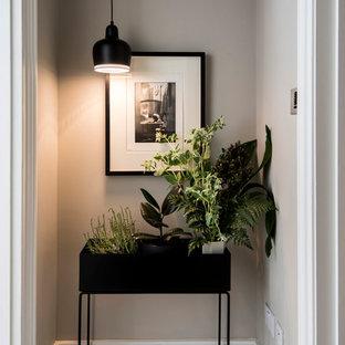 На фото: узкая прихожая в современном стиле с серыми стенами и деревянным полом с