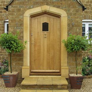 На фото: входная дверь в классическом стиле с одностворчатой входной дверью и входной дверью из дерева среднего тона с