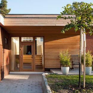Idéer för en mellanstor modern ingång och ytterdörr, med bruna väggar, betonggolv, en enkeldörr och glasdörr