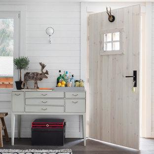 Cette image montre une porte d'entrée nordique avec un mur blanc, un sol en bois brun, une porte simple et une porte en bois clair.