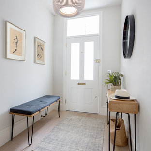 Photo of a medium sized contemporary hallway in London with grey walls, light hardwood flooring, a single front door, a white front door and beige floors.