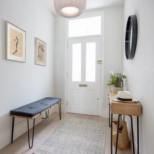 Imagen de hall contemporáneo, de tamaño medio, con paredes grises, suelo de madera clara, puerta simple, puerta blanca y suelo beige
