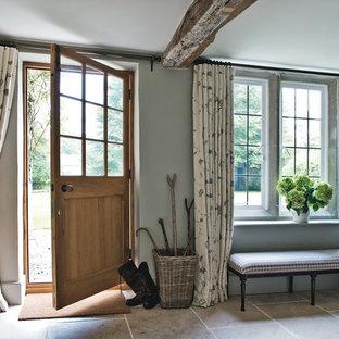 Bild på en lantlig entré, med grå väggar, kalkstensgolv, en enkeldörr och mellanmörk trädörr