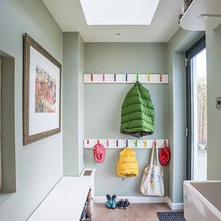 Réalisation d'une entrée design de taille moyenne avec un vestiaire, un mur vert, un sol en carreau de terre cuite et un sol orange.