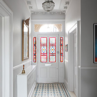 Réalisation d'une grand entrée tradition avec un mur blanc, un sol en carrelage de céramique, une porte simple, un sol multicolore, un couloir, une porte en verre et un plafond à caissons.