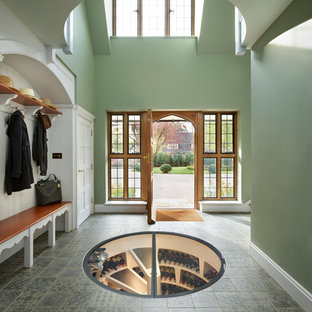 Design ideas for a traditional foyer in Other with green walls, a single front door, a medium wood front door and grey floors.