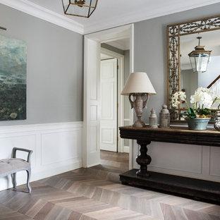 Exemple d'un grand vestibule chic avec un sol en bois clair, un sol gris et un mur gris.